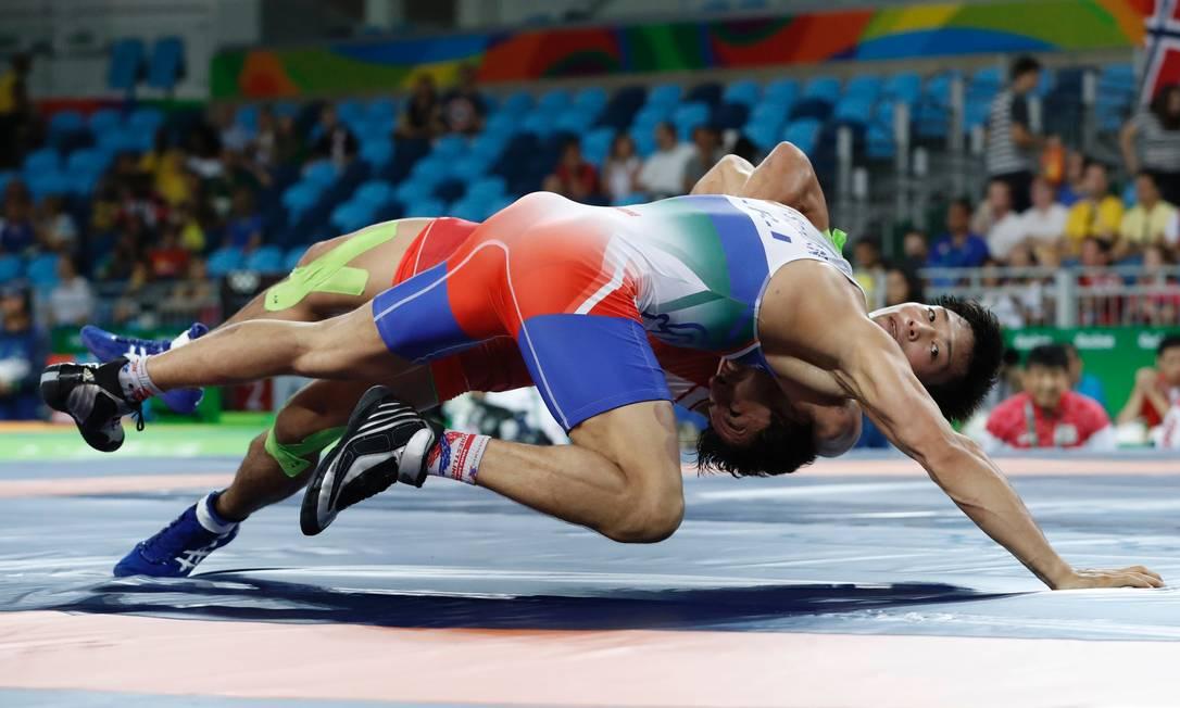 Também pelas classificatórias da categoria 59kg, o japonês Shinobu Ota lutou contra o iraniano Hamid Mohammad Soryan (de azul) JACK GUEZ / AFP