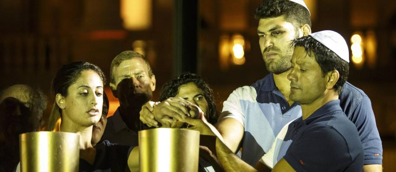 Atletas israelenses acendem uma das velas em homenagem às 11 vítimas dos atentados de 1972 em Munique Foto: Fernando Lemos / O Globo