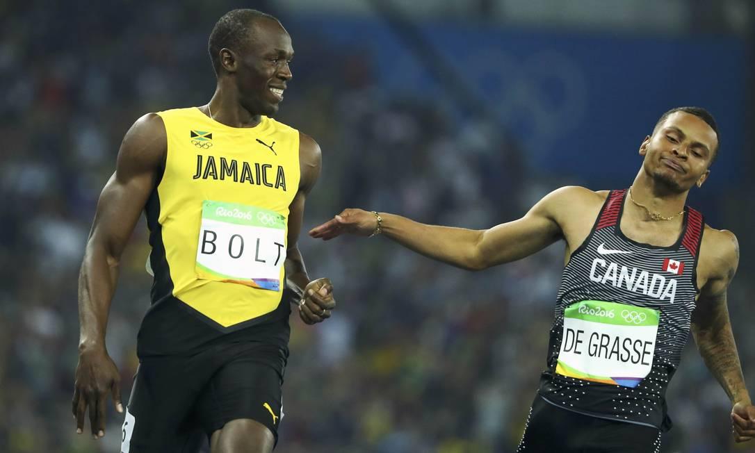 Usain Bolt e o canadense Andre De Grasse em momento de descontração na pista LUCY NICHOLSON / REUTERS