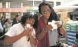 Amigas nigerianas experimentam tapioca na feira
