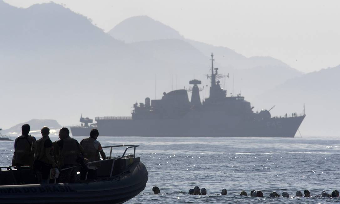 Com navio ao fundo e o bote de socorro perto delas, as nadadoras vão em busca da medalha olímpica TOBY MELVILLE / REUTERS