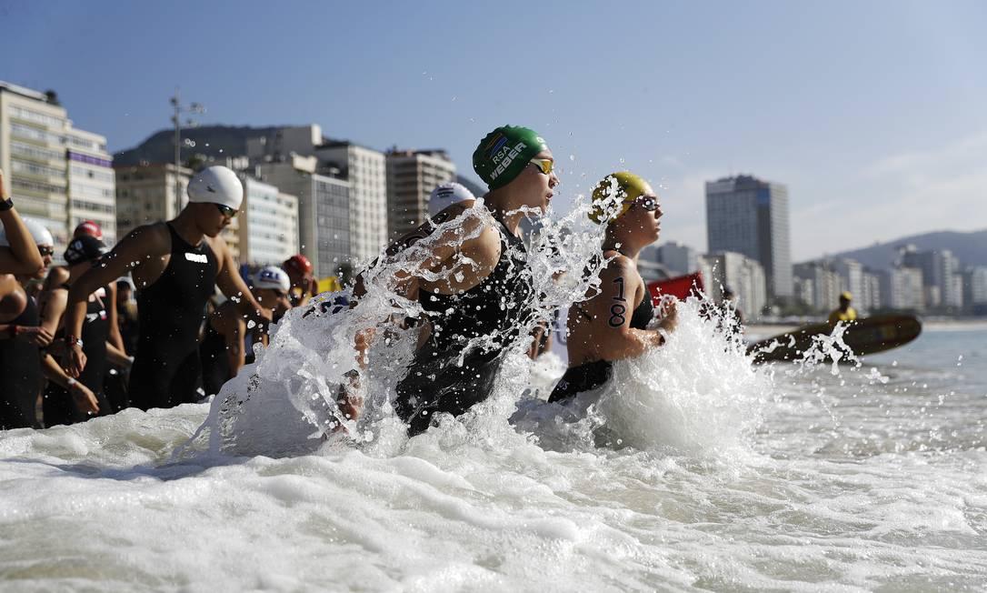 Michelle Weber , da África do Sul, de touca verde, entra no mar junto com outras competidoras David Goldman / AP