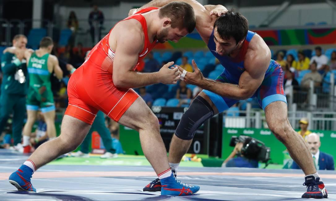 O russo Davit Chakvetadze, de vermelho, luta com o azerbaijano Saman Ahmed Tahmasebi pelas classificatórias da luta olímpica JACK GUEZ / AFP