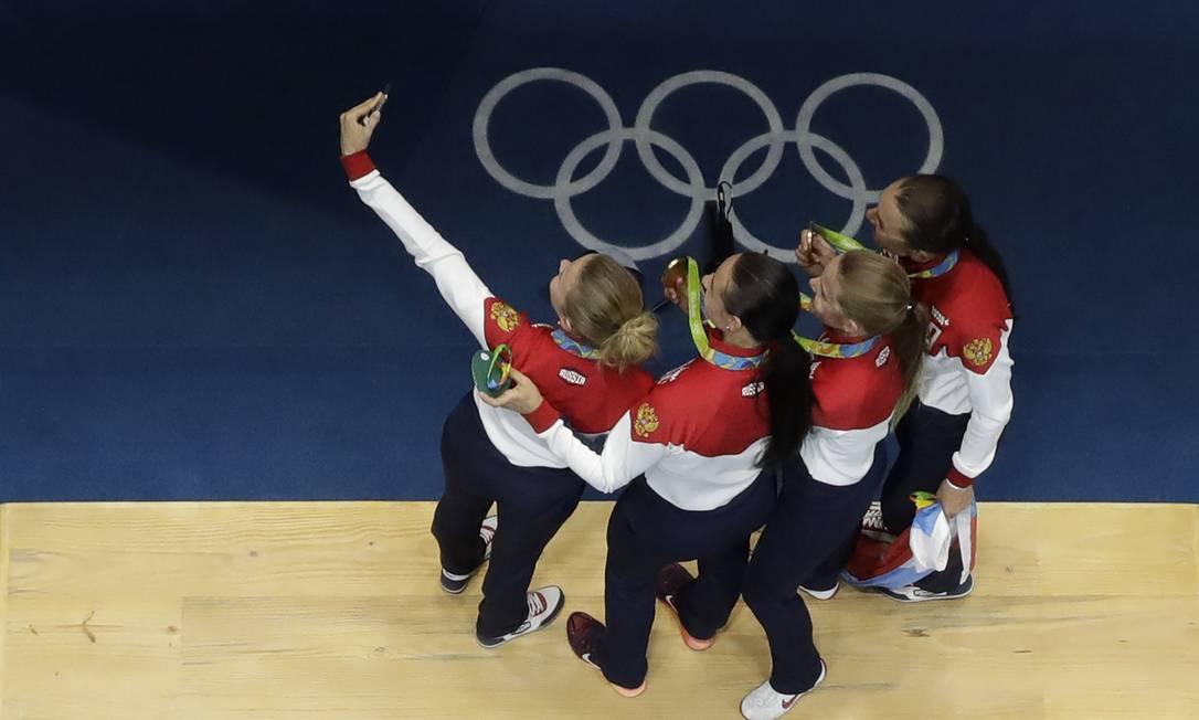 Equipe de esgrima da russa tira selfie no pódio Andrew Medichini / AP