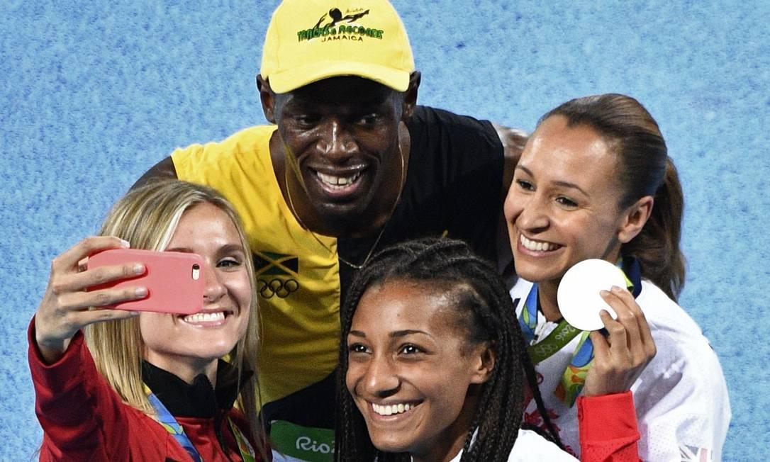 Usain Bolt posa para selfie com atletas MARTIN BUREAU / AFP