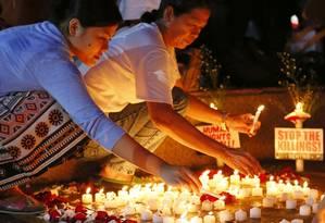 Ativistas de direitos humanos acendem velas por vítimas de execuções extra-judiciaiis nas Filipinas Foto: Bullit Marquez / AP