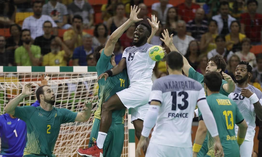 O francês Luc Abalo e o brasileiro Thiagus dos Santos disputam a bola Matthias Schrader / AP