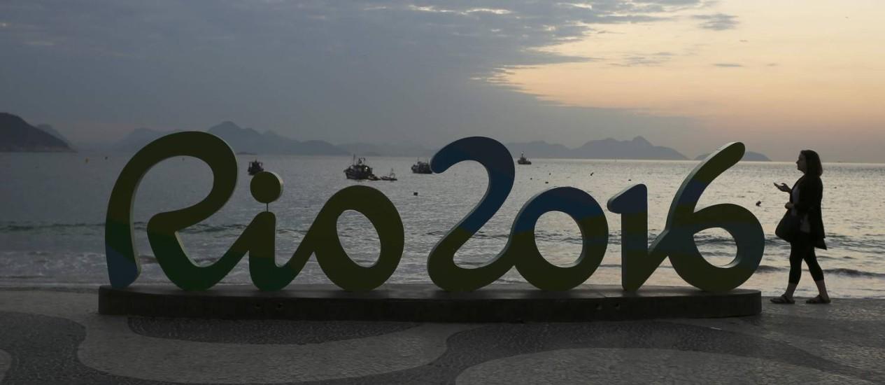 Mulher ao lado do símbolo da Olimpíada do Rio, em Copacabana Foto: Bruno Kelly / Reuters