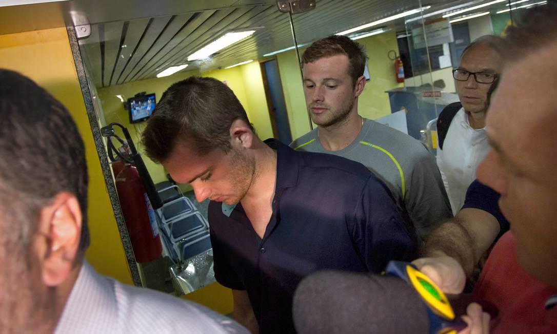 Nadadores americanos Gunnar Bentz (à esquerda) e Jack Conger deixam a delegacia do aerporto Foto: Mauro Pimentel / AP