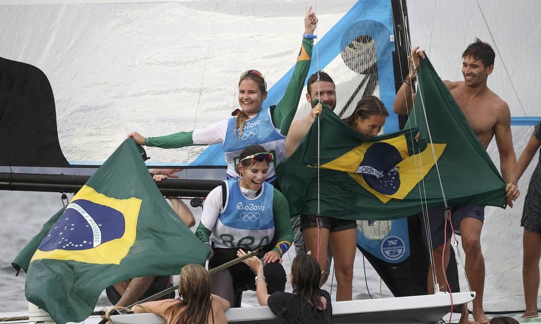 A torcida brasileira mergulhou na Baía de Guanabara para comemorar o ouro de Martine e Kahena com as duas campeãs BENOIT TESSIER / REUTERS