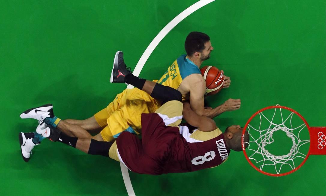 Kevin Lisch, da Austrália e David Cubillan, da Venezuela se chocam durante partida de basquete na Arena Carioca JIM YOUNG / AFP