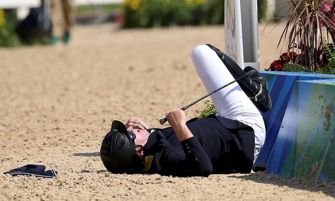 Scott Keach, da Austrália, cai do cavalo durante prova individual do hipismo TONY GENTILE / REUTERS