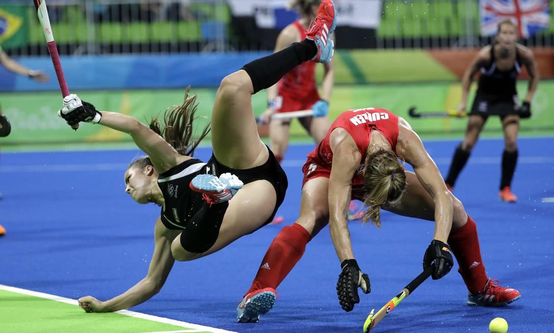 Rose Keddell, da Nova Zelândia (esquerda), cai após choque com a britânica Crista Cullen, em partida de hóquei Hussein Malla / AP