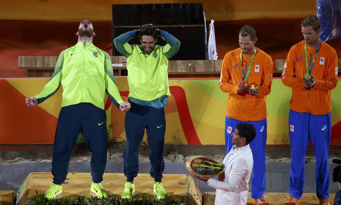 No pódio, Alison vibra com o ouro olímpico e Bruno, com as mãos na cabeça, parece não acreditar no feito CARLOS BARRIA / REUTERS