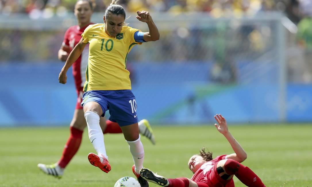 Marta tenta escapar para o ataque pela seleção brasileira, mas leva o carrinho da jogadora canadense FERNANDO DONASCI / REUTERS