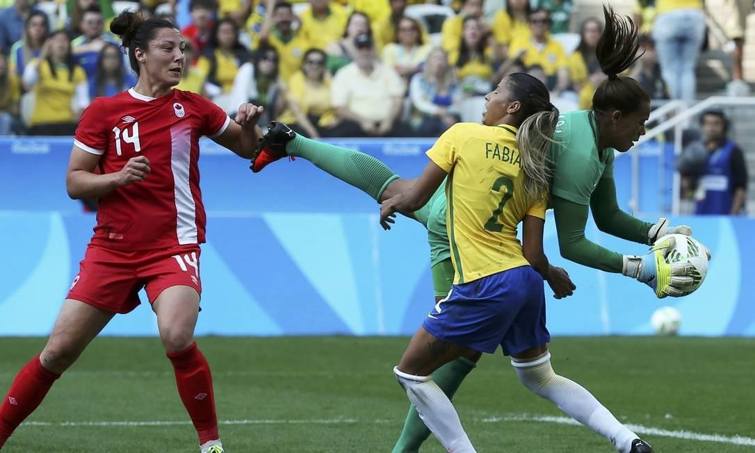 A goleira Barbara, do Brasil, realiza defesa, observada por Fabiana e Melissa Tancredi Foto: PAULO WHITAKER / REUTERS