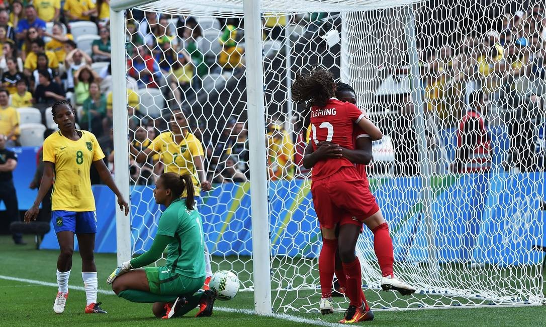 No Itaquerão, em São Paulo, Rose (encoberta) e Sinclair (12) se abraçam e festejam gol do Canadá sobre o Brasil na decisão do bronze na Olimpíada do Rio Foto: NELSON ALMEIDA / AFP