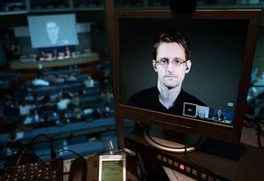 Em 2015, ex-analista da NSA Edward Snowden, participa de transmissão ao vivo em tela de computador Foto: FREDERICK FLORIN / AFP