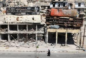 Pessoas caminham em frente a ônibus destruídos sobre prédios que servem de barricadas em Aleppo, na Síria Foto: ABDALRHMAN ISMAIL / REUTERS