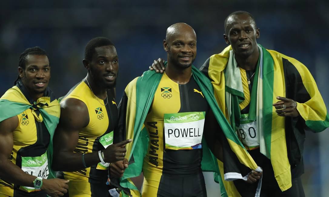 O campeões Yohan Blake, Nickel Ashmeade, Asafa Powell e Usain Bolt comemoram o ouro envoltos por bandeiras da Jamaica Jorge William / Agência O Globo