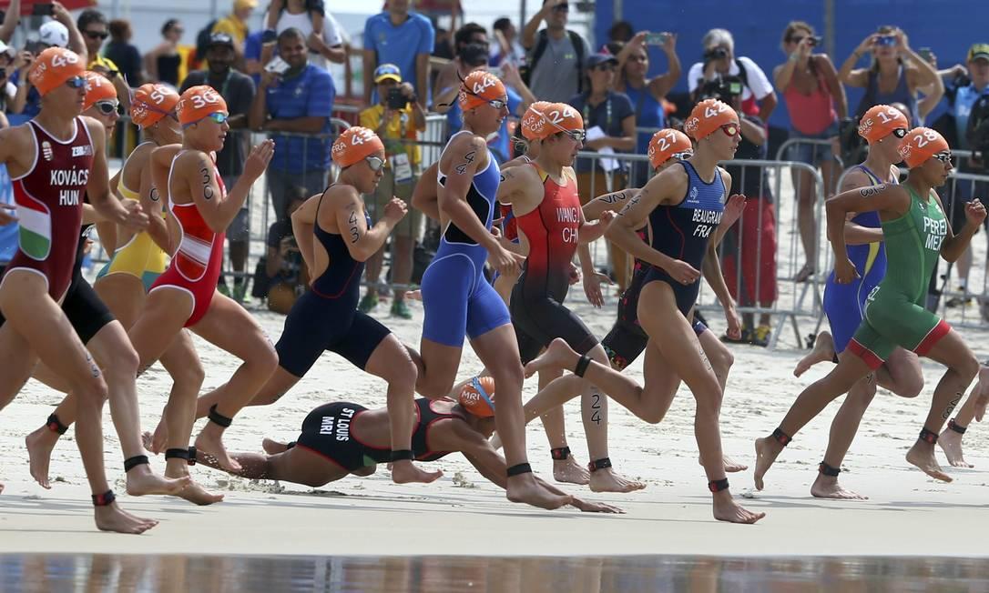 Triatletas partem para a prova no mar. Uma das competidoras cai na largada Carolos Barria / Reuters