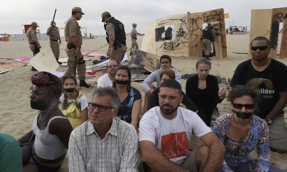 Ativistas do Rio de Paz sentam na areia enquanto guardas municipais removem instalação na Praia de Copacabana Ricardo Moraes / Reuters