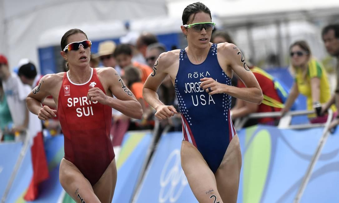 A americana Gwen Jorgensen é seguida de perto pela suiça Nicola Spirig na última parte do triatlo feminino JEFF PACHOUD / AP
