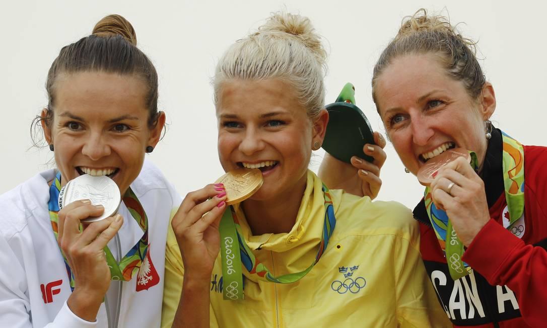 Jenny Rissveds da Suécia, ao centro, ganhou a medalha de ouro, Maja Wloszczowska da Polónia, à esquerda ganhou a de prata e Catharine Pendrel do Canadá ganhou a de bronze Patrick Semansky / AP