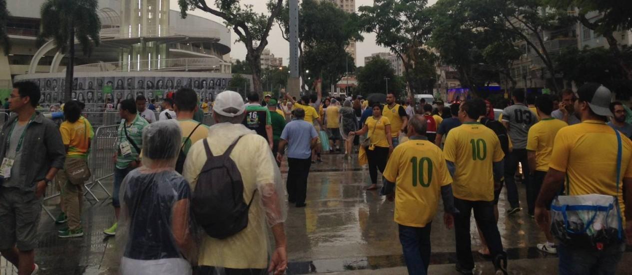 No entorno do Maracanã, depois de uma rápida chuva, torcedores chegam para ver a decisão do ouro olímpico no futebol entre Brasil e Alemanha Foto: Tatiana Furtado / Agência O Globo