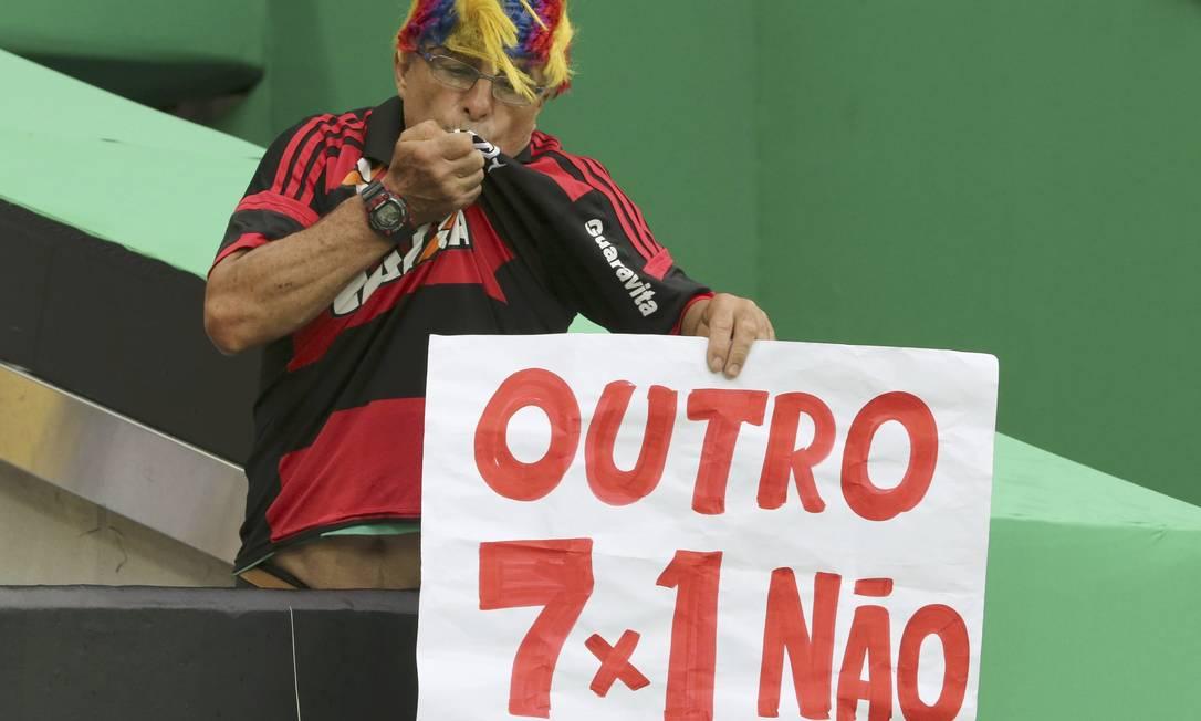 """Torcedor beija a camisa do Flamengo e segura cartaz que diz: """"Outro 7x1 não"""" PAULO WHITAKER / REUTERS"""