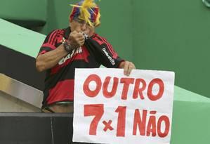 Torcedor beija a camisa do Flamengo e segura cartaz que diz: