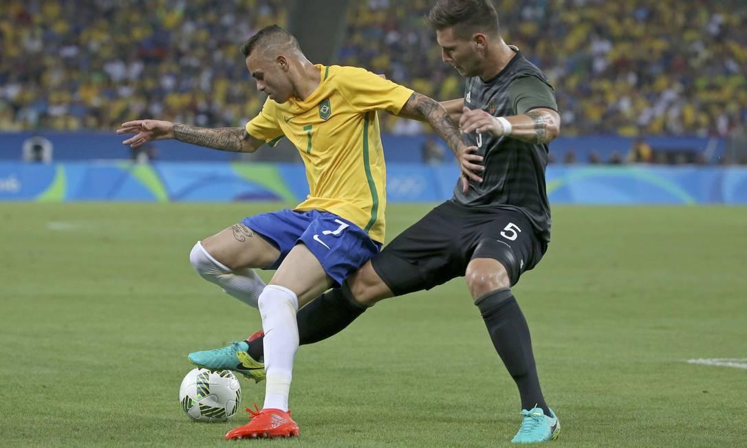 Luan protege a bola e o alemão Niklas Suele estica a perna para roubá-la do atacante brasileiro PAULO WHITAKER / REUTERS