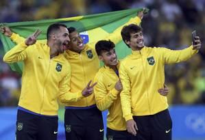 Renato Augusto, Marquinhos, Zeca e Rodrigo Caio fazem selfie no pódio: ouro no futebol Foto: BRUNO KELLY / REUTERS