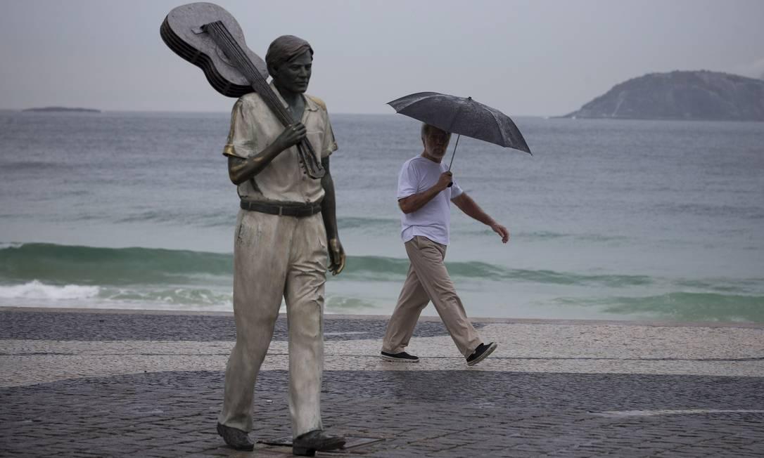 Em dia chuvoso no encerramento da Rio-2016, morador observa estátua de Tom Jobim, na orla da Praia de Copacabana Márcia Foletto / Agência O Globo