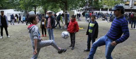 Refugiados jogam futebol enquanto esperam para preencher formulários para pedido de asilo em Berlim Foto: FABRIZIO BENSCH / REUTERS