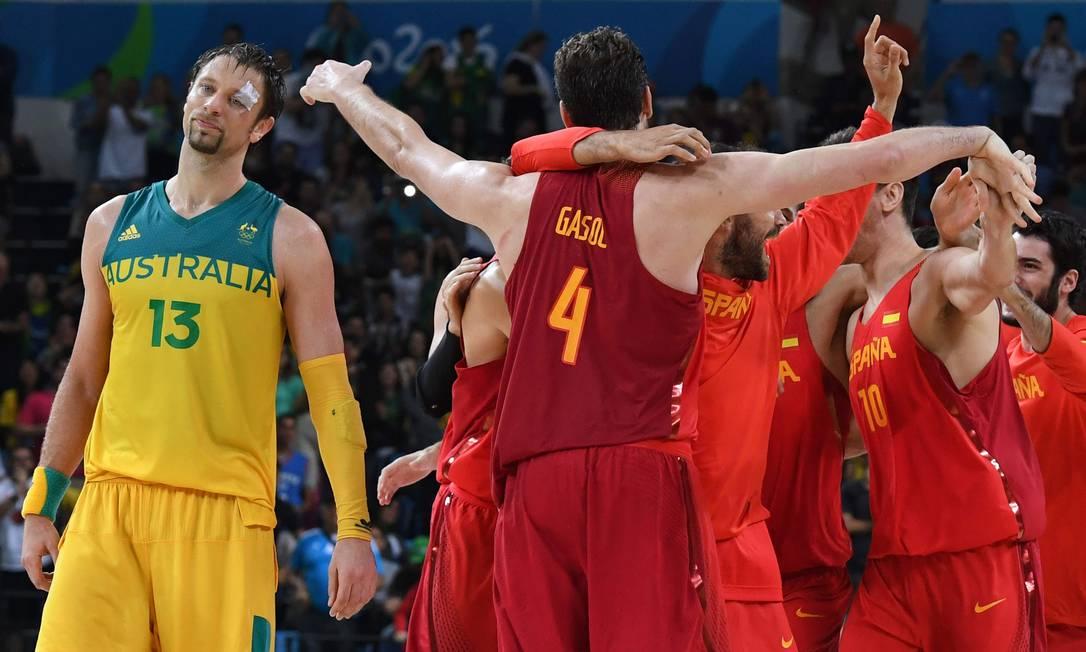 O australiano David Andersen lamenta, enquanto o time da Espanha comemora a vitória MARK RALSTON / AFP