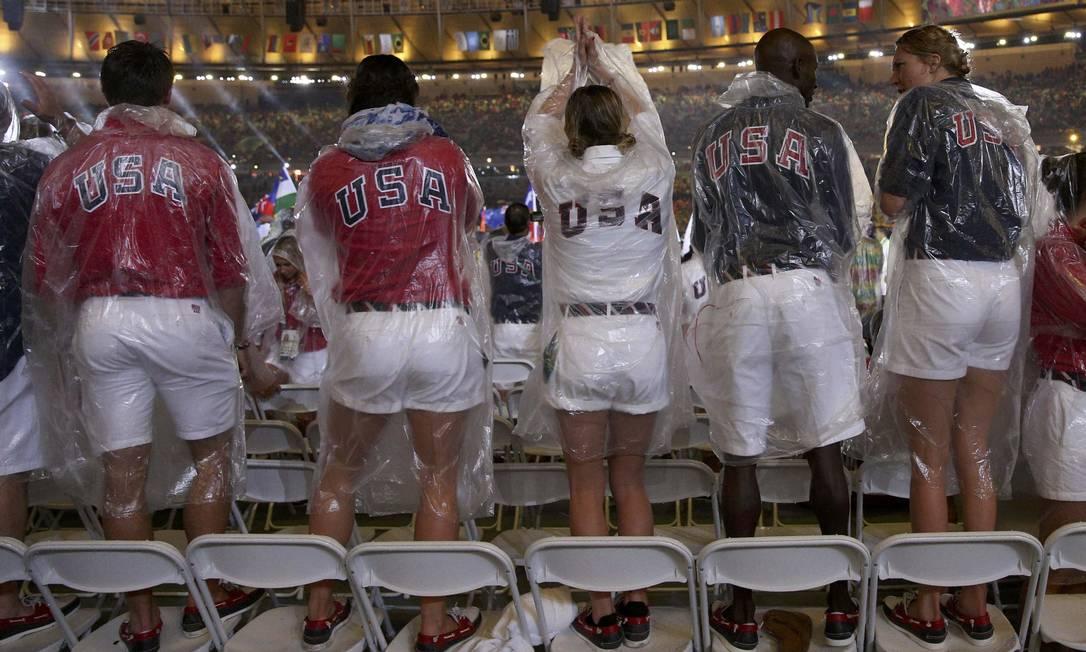 Atletas dos EUA sobem em cadeiras para curtir a festa e a chuva depois do desfile STOYAN NENOV / REUTERS