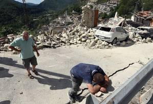 Um homem se debruça sobre uma parede na cidade de Pescara del Tronto, no Centro da Itália, após terremoto Foto: Crocchioni / AP