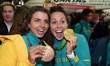 As atletas australianas Jessica Fox e Chloe Esposito exibem suas medalhas no retorno a Sydney. Muita felicidade e recomendação de sexo seguro Foto: SAEED KHAN / AFP