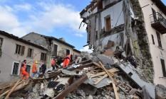 Homens fazem busca nos escombros de Arquata del Tronto, na Itália central Foto: STR / AFP
