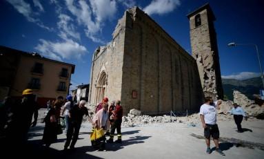 Pessoas passam em frente a igreja danificada após terremoto em Amatrice, na Itália Foto: FILIPPO MONTEFORTE / AFP