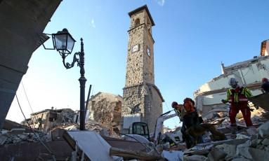 Socorristas trabalham em frente a torre de relógio, que marca hora do terremoto, em cidade italiana de Amatrice Foto: STEFANO RELLANDINI / REUTERS