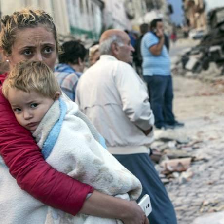 Mulher segura criança em rua de Amatrice devastada pelo abalo Foto: Massimo Percossi / AP/Massimo Percossi