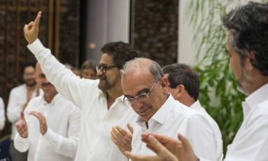 Iván Márquez, porta-voz das Farc (de mão erguida), e Humberto de la Calle (chefe negociador do governo) são aplaudidos Foto: Desmond Boylan / AP