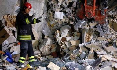 Bombeiro busca vítimas em escombros de casa devastada após terremoto na cidade italiana de Amatrice Foto: Reuters / Stefano Rellandini