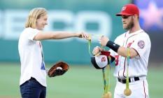 Bryce Harper segura as medalhas de Katie Ledecky para que ela possa fazer o arremsso no jogo entre Baltimore Orioles e Washington Nationals Foto: Greg Fiume / AFP