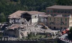 Equipe de resgate e de serviços de emergência usam escavadeira para procurar vítimas sob os escombros de um edifício em Amatrice Foto: FILIPPO MONTEFORTE / AFP