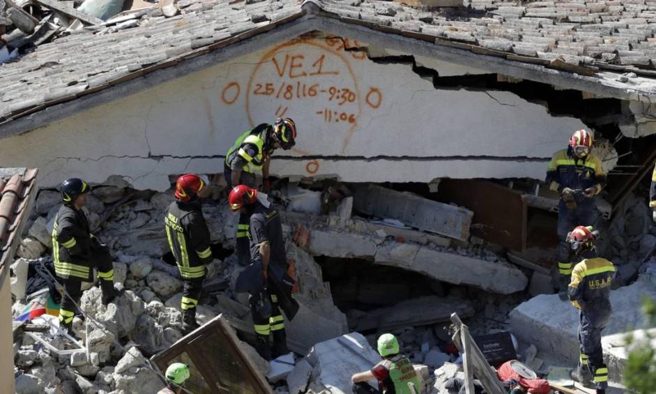 Equipes de resgate marcam o horário do início e do fim das buscas em um prédio de Pescara Del Tronto, Itália. Eles travam uma corrida contra o tempo nas três cidades mais atingidas pelo terremoto Foto: Gregorio Borgia / AP