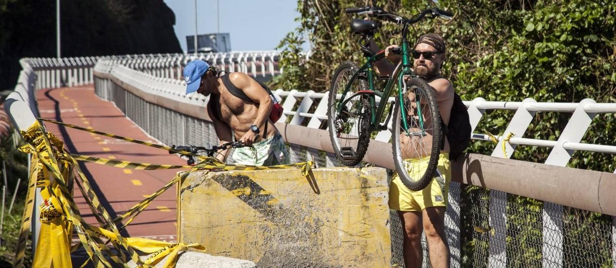Ciclista levanta a bicicleta para conseguir passar pela barricada Foto: Hermes de Paula / Agência O Globo