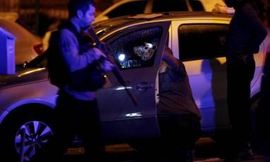 Agentes realizam a perícia em carro de policial atingido por disparos Foto: Pedro Teixeira / Agência O Globo
